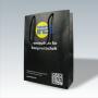 Exklusive Papiertasche in Schwarz mit mehrfarbigem Druck und verstärkten Baumwollkordeln