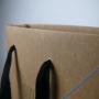 Exklusive Papiertasche aus Kraftpapier mit schwarzen Tragebändern in Nahaufnahme