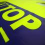 """Plastiktüte """"TOP Energy"""" in Gelb mit dunkelblauem Druck und verstärkten Grifflöchern in Nahaufnahme"""