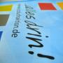 PP Non Woven Tasche mit farbigen, matt laminierten, verlängerten Seitenteilen, die die Trageschlaufen bilden in Nahaufnahme.