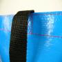 Glänzend laminierte PP Woven Tasche mit zwei unterschiedlich bedruckten Fronten und langen Kunststofftragebändern in Nahaufnahme