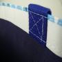 Kraftpapier + Non Woven Tasche in Weiß mit blauen Akzenten und langem Trageband in Nahaufnahme